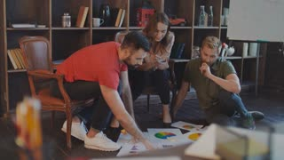 Creative businesspeople working with company strategy documents on office floor. Business professionals planning strategy on floor. Creative people planning startup business on floor in office