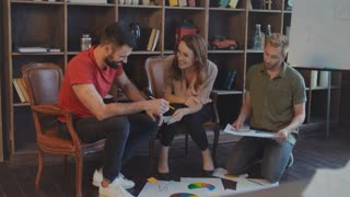 Creative team working with documents and diagrams on floor in office. Successful business people brainstorming ideas in office. Casual business group analyzing market data. Brainstorming team work
