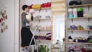 Creative woman shelving thread spool on stillage in textile store. Woman seller lying on shelve yarn balls in sewing workshop. Woman in textile shop