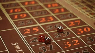 Croupier hand taking and throwing red dices on gambling table. Close up brown surface with classic betting grid. Gambling game in craps at vegas casino. Player hand throwing three dices on table
