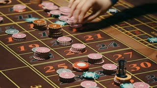 Croupier hands removing casino chips from gambling table. Casino roulette table with classic betting grid. Close up casino dealer hands clean up table from game bets. Gambling game in casino