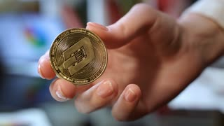 Cryptocurrency business concept. Close up of gold altcoin in hand. World cryptocurrency business. Modern blockchain technology. Investment in dashcoin cryptocurrency. Woman hand holding gold dash coin