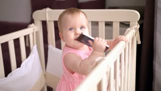 Cute baby eating mobile phone. Little child with smartphone in mouth. Toddler girl enjoy modern technology. Adorable kid licks mobile. Smart mobile gadget in crib