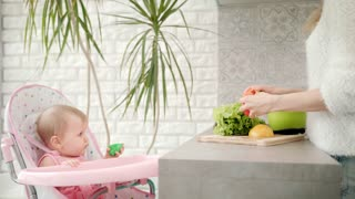 Cute child looking on mother cooking food. Mom with baby on kitchen. Mom and baby preparing healthy diet food. Female cooking vegetables for kid. Mother cooking with daughter in white kitchen
