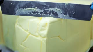 Cutting food ingredient. Close up of cutting butter block with knife. Ice cream ingredients. Milk products. Knife cutting butter block. Margarine butter cut