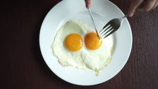 Cutting fried eggs with knife and fork on white plate at wooden table. Eating eggs. Traditional breakfast. Eating fried eggs with knife and fork. Top view of fried eggs on white plate