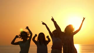 Dancing woman party at beach sunset. Playful girls silhouettes on summer sunset. Enjoy summertime at summer party. Woman have fun with hands up at sun set. Jumping woman silhouettes
