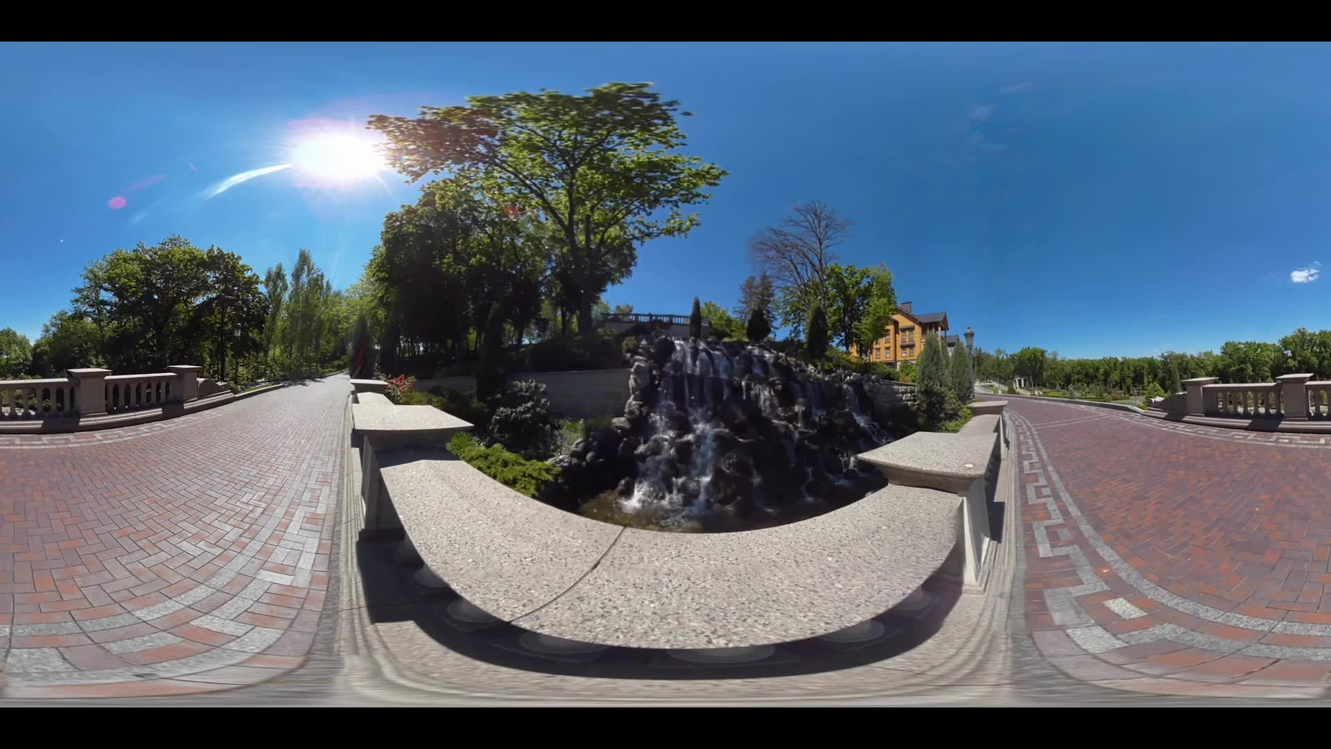 Decorative waterfall on background stones in cottage village. Waterfall landscape in cottage village 360 panorama. Panoramic view of stone pathway in summer garden. 360 degree view of stone walkway