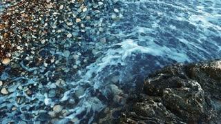 Deep blue sea water beating of rocky coastline. Close up blue ocean breaking waves. Foamy surf on pebble beach. Sea waves breaking along the shore. Foam waves on rocky shoreline