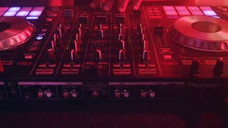 DJ control music console in nightclub. DJ mixer player. Close up DJ control sound console of disco. Disc jockey turntables and mixing deck with colored illuminated. DJ hands mixing music