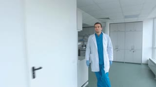 Doctor walking corridor. Steadyshot of medical worker in laboratory corridor. Laboratory man go through white hallway. Scientist in lab coat go hospital corridor