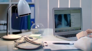 Doctor working with xray on laptop at workplace late. Close up of medical doctor table. Female doctor check xray picture at laptop screen. Radiologist check x-ray picture