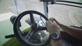 Driver farming tractor hands on steering wheel during plowing field. View from inside cab agricultural machinery driver turn steering wheel and pushing buttons on control joystick