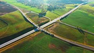 Drone view cars moving on highway junction. Cars driving on freeway interchange. Aerial landscape cars traffic at highway intersection. Landscape road junction on highway. Aerial road junction