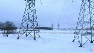 Drone view electric towers in winter field. Electricity pylons and transmission lines. Aerial view high voltage power lines near highway. Electricity lines