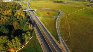 Drone view road intersection and cars traffic on highway. Aerial view road junction highway. Car traffic on highway. Cars driving on road circle. Cars driving on country road view from above