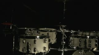 Drum set on dark background. White drum kit on black background. Percussion instruments. Percussion drums. Instruments drummer. Drummer musical plate. Percussion tools