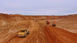 Dump truck driving through industrial sand pit territory. Drone view. Crawler excavator extract sand on quarry. Aerial view of dumper truck transporting sand on quarry. Sand mining aerial view