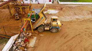 Dump truck dumping sand to sorting conveyor. Sand sorting process on mining conveyor. Aerial view of mining machinery working at sand quarry. Mining equipment for sorting sand. Mining truck