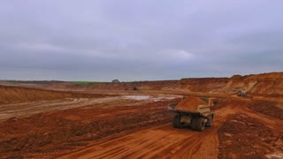 Dumper truck moving along sand quarry. Aerial view of dump truck. Drone view of tipper truck carries sand. Sky view of mining truck on quarry. Tipper trucks on sand pit. Sand transporting