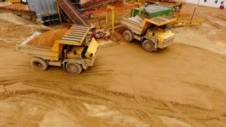 Dumper trucks with sand standing on territory industrial factory. Aerial view. Tipper trucks on industrial plant sky view. View from above cargo trucks on territory sand quarry. Sand work