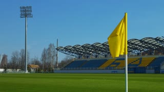 Empty sports stadium landscape. Rows of plastic chairs in open football stadium. Yellow flag blowing in soccer grass. Soccer field with green grass. Sport arena background. Football field on sunny day