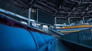 Empty sports stadium with nobody from tribune and big scoreboard. Seating rows in soccer stadium with folded chairs. New plastic colorful seats on grandstand. Modern sports arena with empty fans zone
