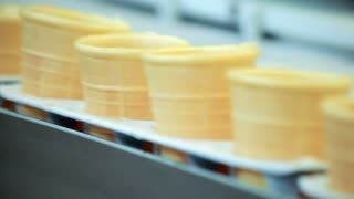 Empty waffle cone on production line. Food factory conveyor belt. Food manufacturing line. Ice cream waffle cup moving on manufacturing line. Food processing plant. Waffle cone on conveyor line