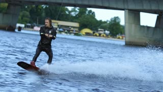 Energy sportsman in black swimsuit wakeboarding. Extreme summertime on river. Wakeboarder surfing across lake. Man water skiing. Man riding wakeboard on river water