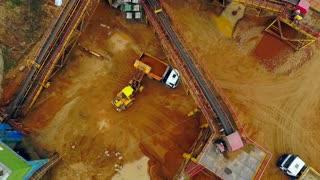 Excavator loader loading sand into dumper truck. Aerial view. Excavator loader working on sandpit. Backhoe excavator loading sand in dumper truck. Wheel loader loading sand in tipper truck. Sand work