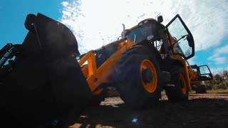 Exposition of new commercial construction equipment. Big orange wheel loader excavator. Close up loader excavator bucket. Sale of professional heavy machinery for mining and earthmoving industry