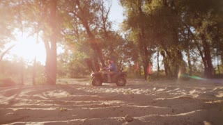 Extreme driver dusting on ATV in slow motion. Man driving quad bike on sand at sunset. Rider spinning on atv in forest at sunset. Tourist driving sand buggy in slow motion.