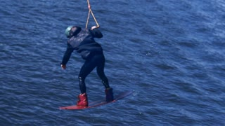 Extreme man studying riding wakeboarding stunt on water. Sportsman training jumping from springboard during wakeboarding tricks. Extreme water sports. Water sports competition. Extreme lifestyle