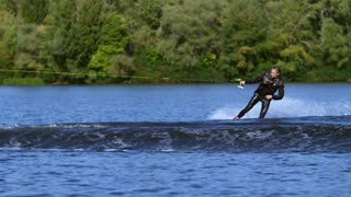 Extreme man wakeboarding in slow motion. Active people. Extreme water sport. Wake boarding rider riding waves. Adrenaline rush on water surface. Water sport activities. Man riding wake