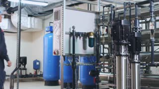 Factory engineer control equipment. Industry engineer equipment. Modern industrial equipment for water purification. Industry worker control water treatment system. Water engineering technology