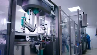 Factory worker at industrial workshop. Operator setting packaging line. Engineer configuring packaging line at pharmaceutical plant. Pharmacy packaging machine. Pharmaceutical factory equipment