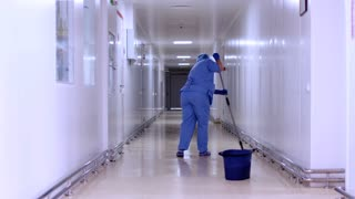 Factory worker mopping floor in hospital corridor. Worker cleaning corridor. Woman in uniform cleaning flour in empty corridor. Female cleaner mopping floor in white corridor hospital
