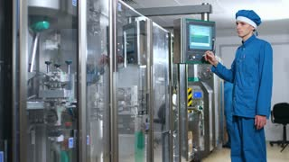Factory worker operate control screen of factory equipment. Male operator working with touch screen panel at manufacturing line. Pharmacist using touch panel. Factory employee use control panel screen