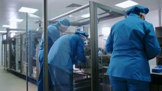 Factory workers repair equipment. Pharmaceutical equipment service. Repair team working on manufacturing line. Manufacturing machine repair by workers team
