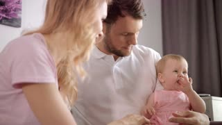 Family leisure time. Sweet baby girl sitting on father hands and playing with mom. Happy family concept. Woman and man with child at home. Parent and child playing togetherness