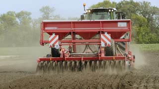 Farm tractor with trailer seeder sowing on plowed land. Sowing machine working on plowed field. Sowing process on agricultural field. Agricultural industry. Plowed field. Cultivated field