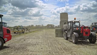 Farming tractor loading haystacks on agricultural field. Process loading straw rolls with help agricultural machinery. Agricultural equipment for loading and transporting haystacks