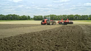 Farming tractor moving on agricultural field for plowing land. Agricultural tractor plowing farming field. Agricultural machinery on plowing field