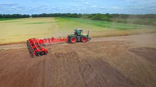 Farming tractor with trailer plowing agricultural field. Agricultural tractor plowing farming field. Process cultivation agricultural field. Agricultural industry. Rural economy. Ploughed field