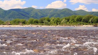 Fast river stream with mountain panorama and stony rapids. Mountain spring landscape with water stream. Idyllic nature landscape. Wild river splash