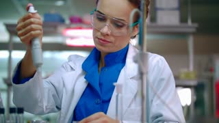 Female chemist doing chemical experiment. Chemical reaction in glass flask. Chemistry woman working with chemical reagents. Chemistry laboratory experiment. Woman chemist in lab