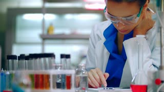 Female chemist scrolling phone in chemical lab. Chemist woman using smart phone in laboratory. Lab chemist looking at phone in chemist lab. Chemistry student looking at mobile phone