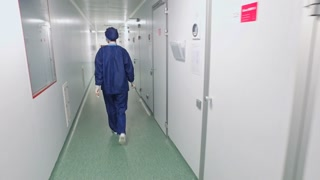 Female doctor in protective uniform walking in hospital corridor. Back view of medical worker walking white corridor. Lab woman in laboratory corridor. Woman in protective clothing go to laboratory