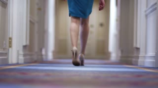 Female feet in high heeled shoes walking along corridor in guest hotel back view. Woman legs in walking on long hallway in luxury hotel back view