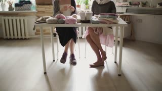 Female feet sitting at table and knitting wool. Two woman friends knitting woolen texture in workshop